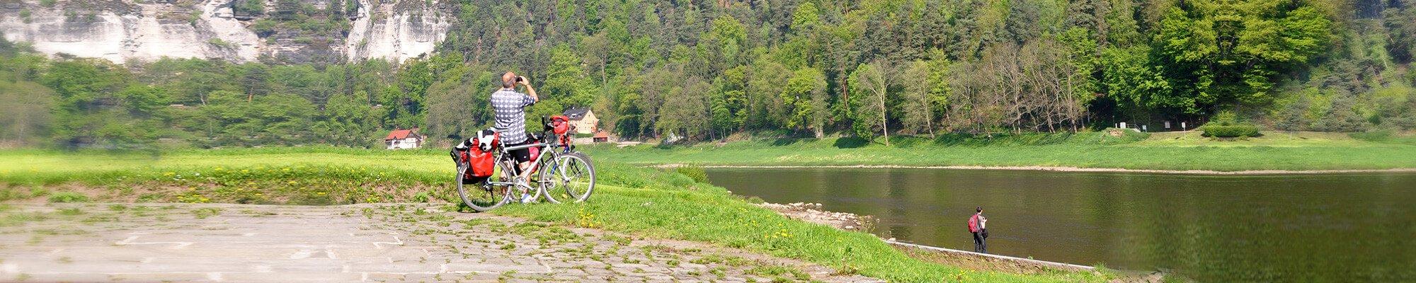 Mann mit Fahrrad schaut auf das Elbsandsteingebirge